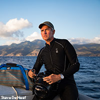 Photo of Brian Skerry wearing a wetsuit on a boat in water with camera ready