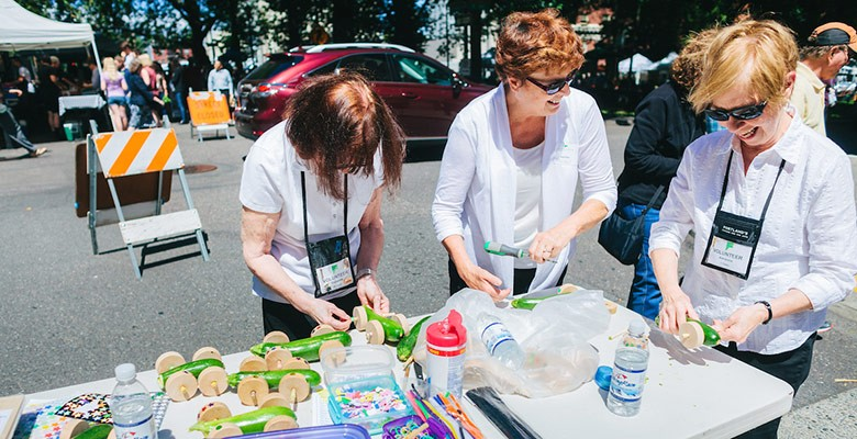 Portland'5 Volunteers prepare vegetable derby cars for the kids to race at Summer Arts on Main Street.