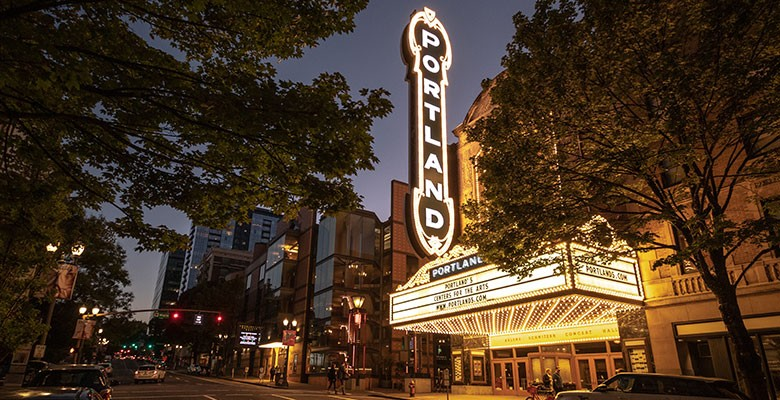 Arlene Schnitzer Concert Hall exterior on Broadway Ave. | Marquee and Portland sign lights at dusk | Photo: Jeremy Jeziorski