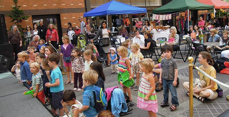 Photo: Children and adults enjoying a free performance at Summer Arts on Main Street.