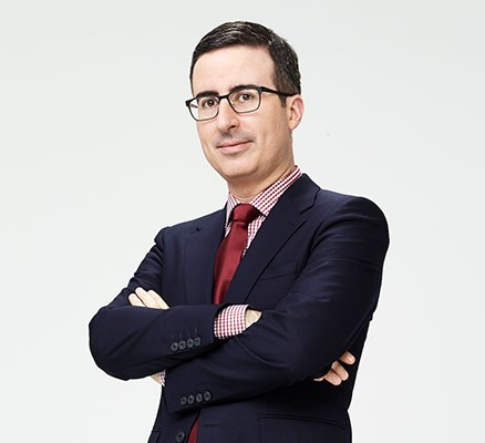 John Oliver publicity photo (standing with arms crossed, wearing a suit)